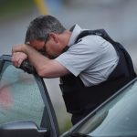 An RCMP officer rests his head at a roadblock in Moncton, N.B. on Thursday, June 5, 2014. Three RCMP officers were killed and two injured by a gunman wearing military camouflage and wielding two guns on Wednesday. Police have identified a suspect as 24-year-old Justin Bourque of Moncton. THE CANADIAN PRESS/Andrew Vaughan